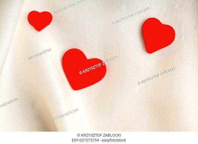 Red wooden decorative hearts on white silk background