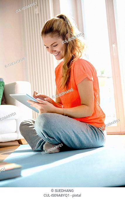Young woman holding and using digital tablet at home