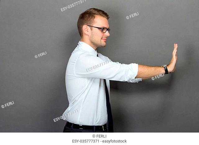 A portrait of a young businessman pushing