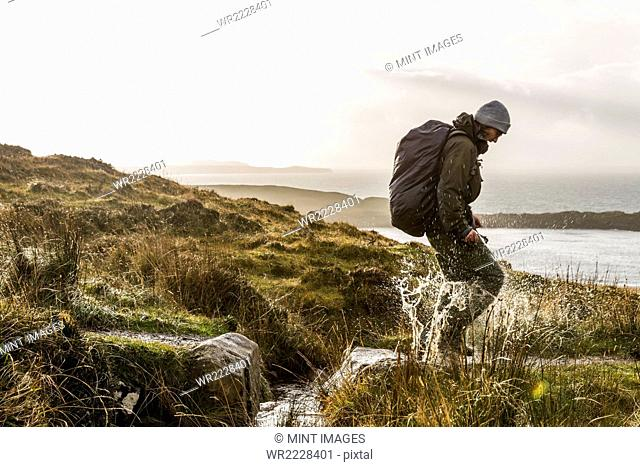 A man with a rucksack and winter clothing leaping across a small stream in an open exposed landscape