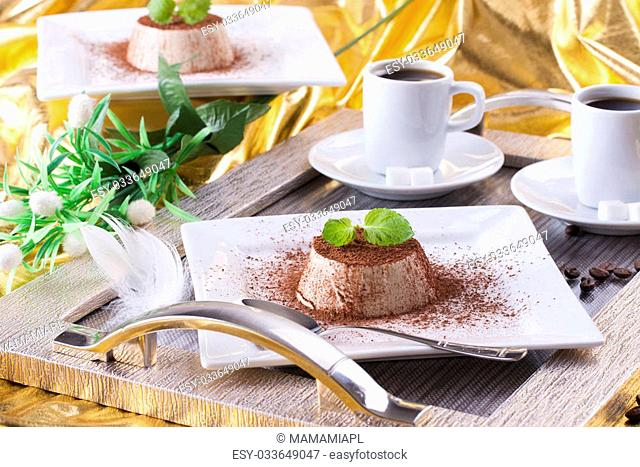 Sweet italian dessert Panna cotta with a cocoa powder and mint on the top on a white plate