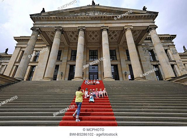 woman taking a picture of children sitting on red carpet at the Konzerthaus Berlin situated on the Gendarmenmarkt, Germany, Berlin