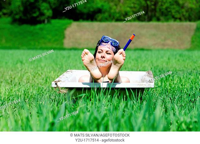 Woman lying in a bathub on a green field and showing her foot and she have a diving mask
