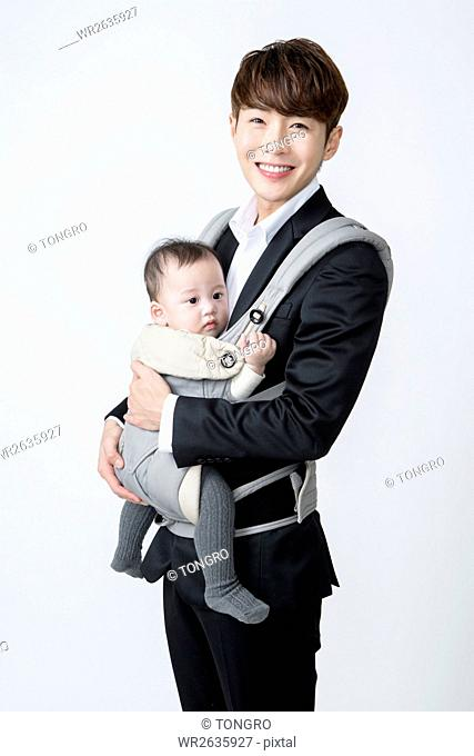 Young smiling businessman hugging his baby