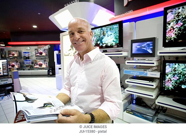 Man with catalogue in electronics shop, smiling, portrait