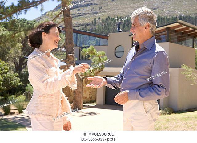 Woman handing keyring to man