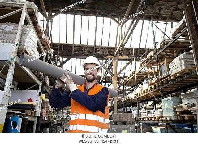 Smiling warehouseman in storehouse carrying pipe