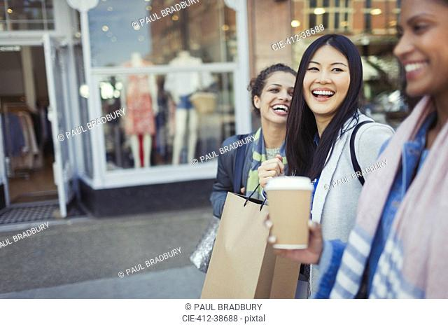 Laughing women friends walking along storefront with coffee and shopping bags