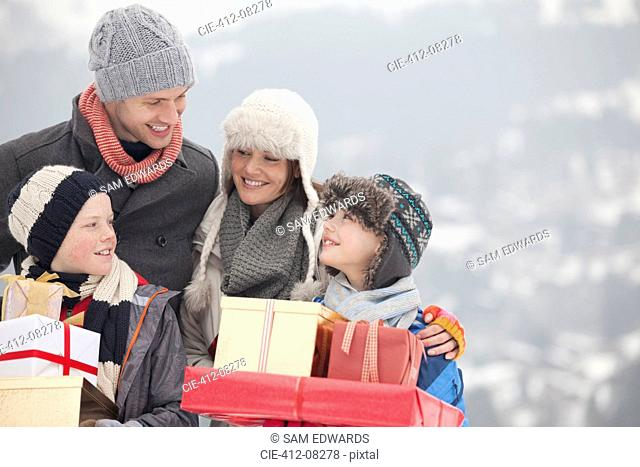 Happy family carrying Christmas gifts in snow