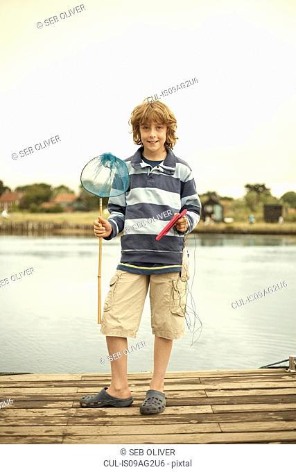 Portrait of boy on pier with fishing net, Southwold, Suffolk, UK