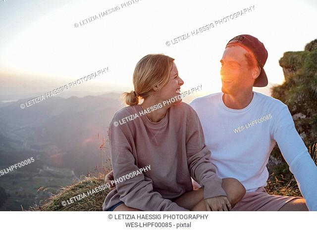 Switzerland, Grosser Mythen, happy young couple on a hiking trip having a break at sunrise