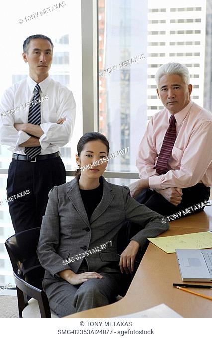 two businessmen, one businesswoman