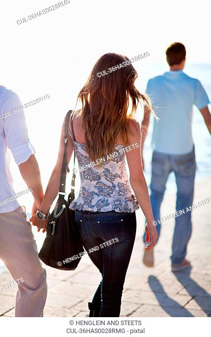 Couple walking hand-in-hand outdoors