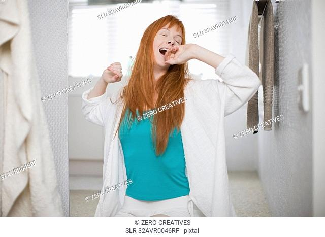 Woman in bathrobe yawning and stretching