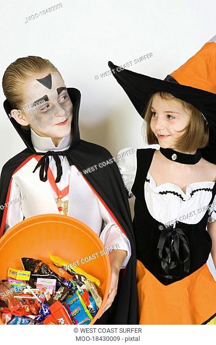 Girl and boy 7-9 wearing Halloween costumes studio shot