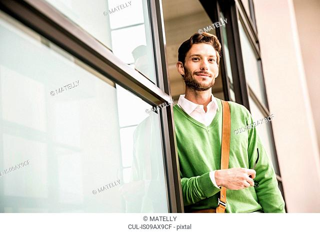 Portrait of cool confident businessman leaning against office doorway
