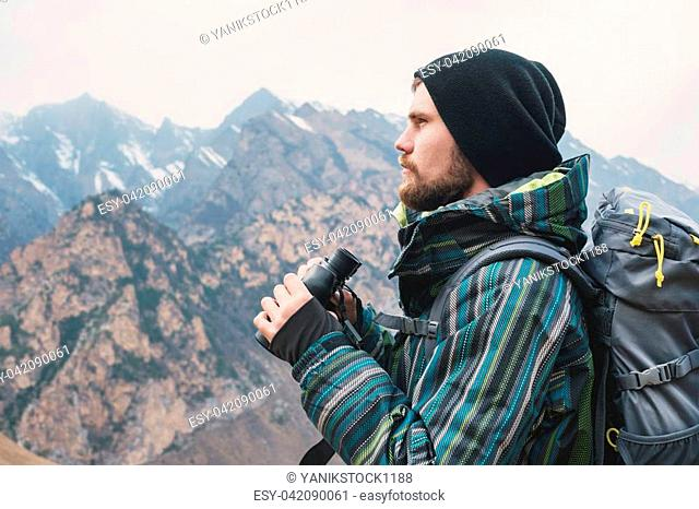 A hipster man with a beard in a hat, a jacket, and a backpack in the caucasian mountains holds binoculars, adventure, tourism, tracking
