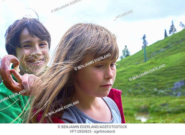 Young boy holding pretzel behind girl