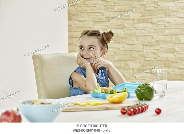 Smiling girl at table packing lunchbox with healthy food