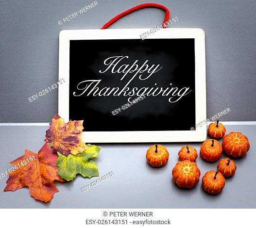 Happy Thanksgiving on wooden board with pumpkins and leaves