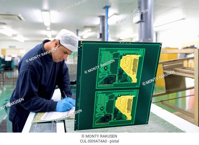 Worker creating circuit board printing machine in circuit board factory