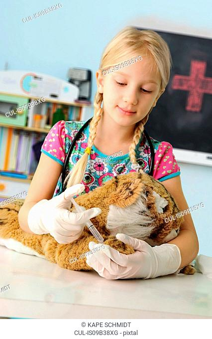 Girl pretending to be vet giving toy tiger syringe injection