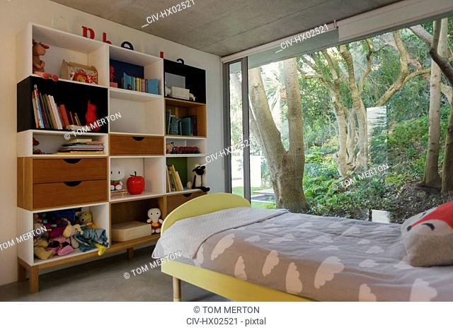 Home showcase interior child's bedroom with view of trees in garden