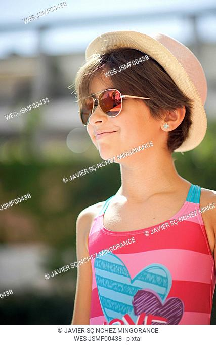 Portrait of young girl with sunglasses and sun hat, looking sideways