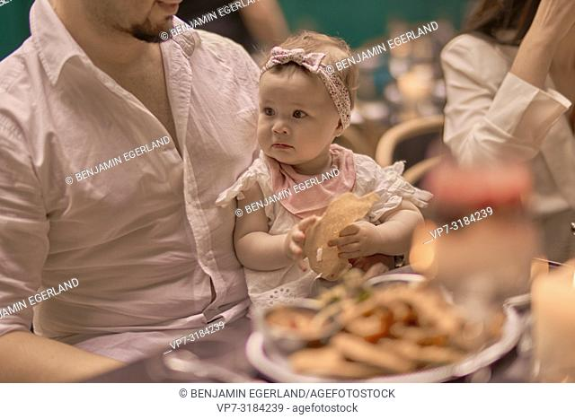 father with baby eating in restaurant, Vegan Oriental, Kismet, in Munich, Germany