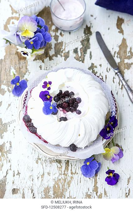 A festive pavlova with berries and pansies