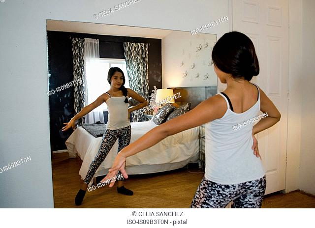 Young girl at home, practising dance moves in front of mirror