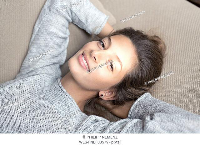 Portrait of smiling woman lying on couch
