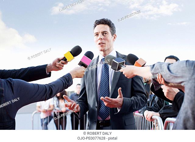 Politician talking into reporters' microphones