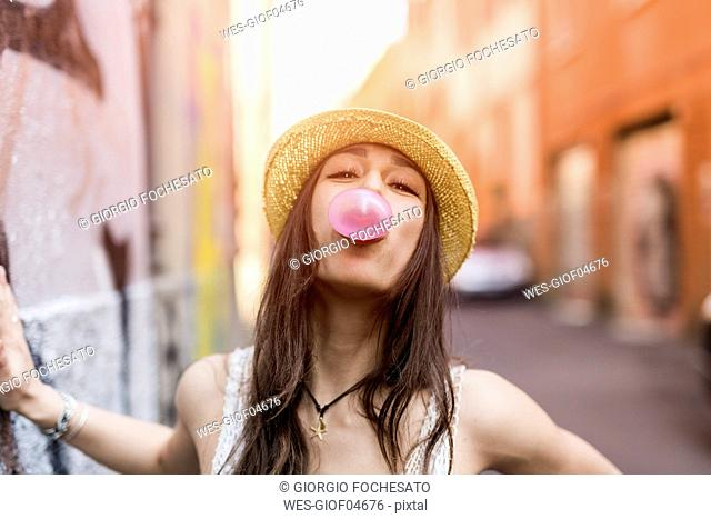 Portrait of young woman blowing pink bubble gum