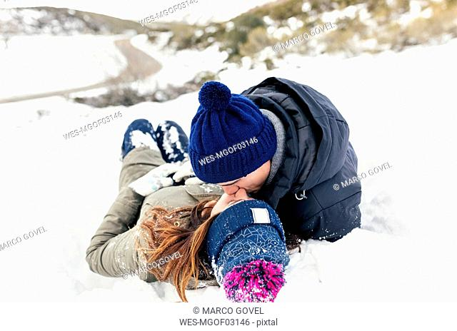 Young couple kissing in the snow