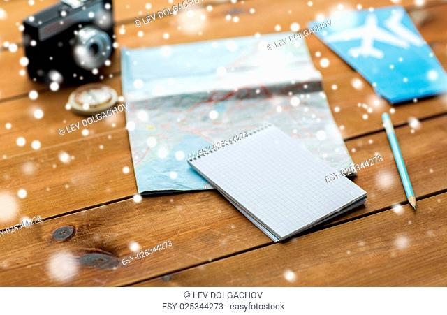vacation, tourism, travel and winter holidays concept - notepad with map, camera and airplane tickets over snow