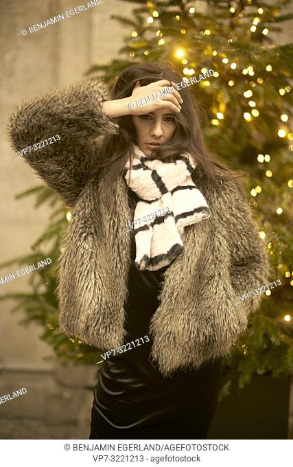 confident playful young woman in front of Christmas tree lights, wearing fashionable winter clothes and scarf, in city Munich, Germany