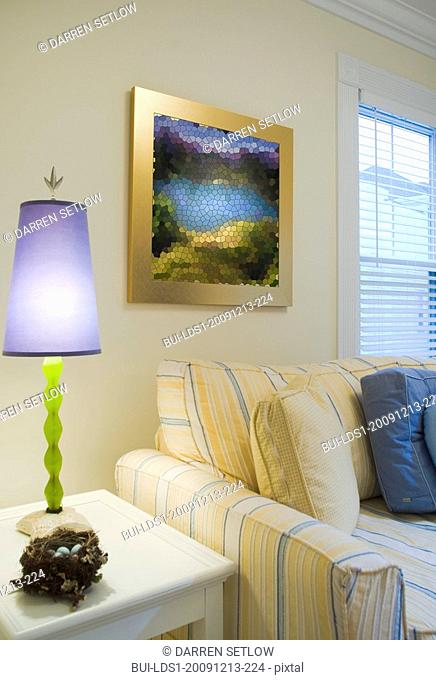 Purple lamp on end table near yellow and blue striped sofa