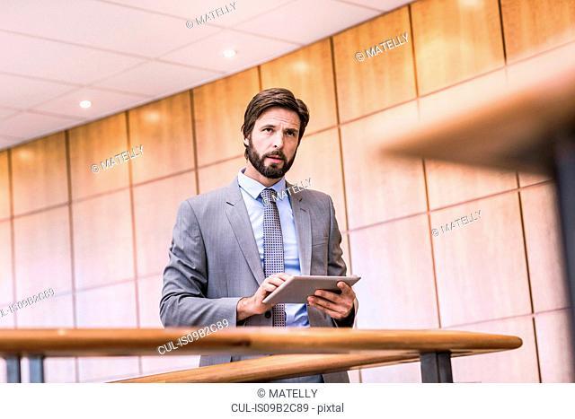 Businessman using digital tablet touchscreen on office balcony