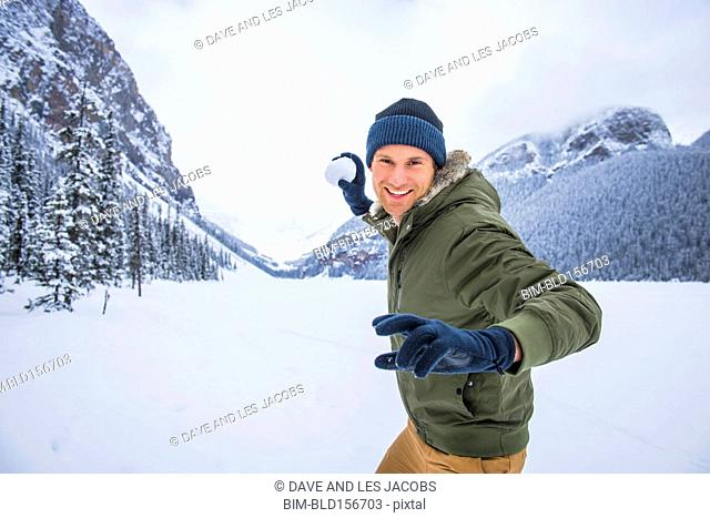 Caucasian man throwing snowball near mountains, Lake Louise, Alberta, Canada