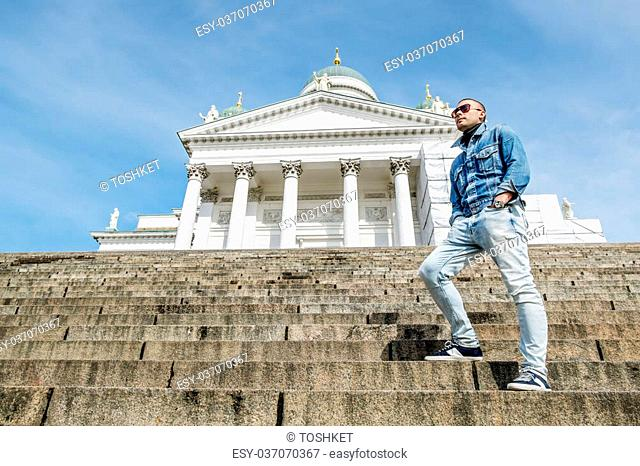 man poses on the granite stairs at the Cathedral on the Senate square in Helsinki Finland