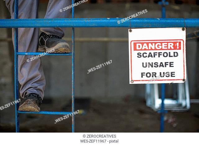 Construction worker climbing scaffold ladder