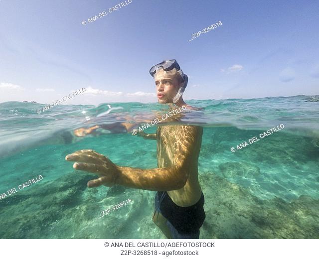 Young man in snorkelling mask dive Underwater El Calo de San Agusti Formentera island Balearics Spain