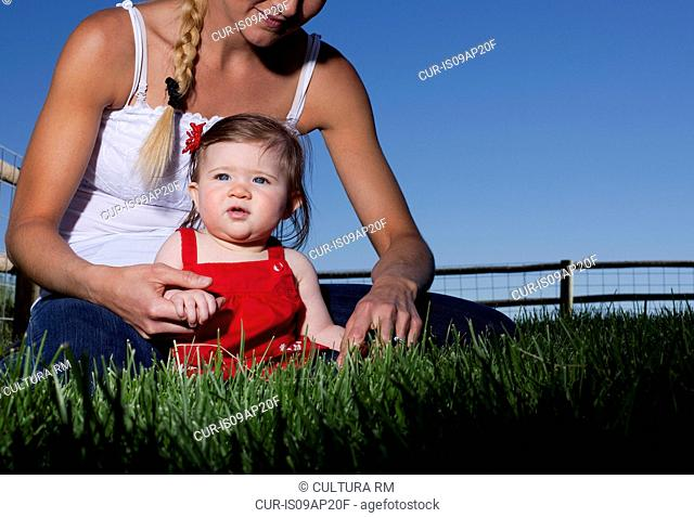 Portrait of mid adult woman sitting on grass with toddler daughter