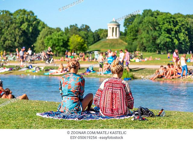 People enjoying the summer, sunbathing, swimming in river Izar and relaxing on green of the Englischer Garten in Munich, Germany on a sunny summer holiday day