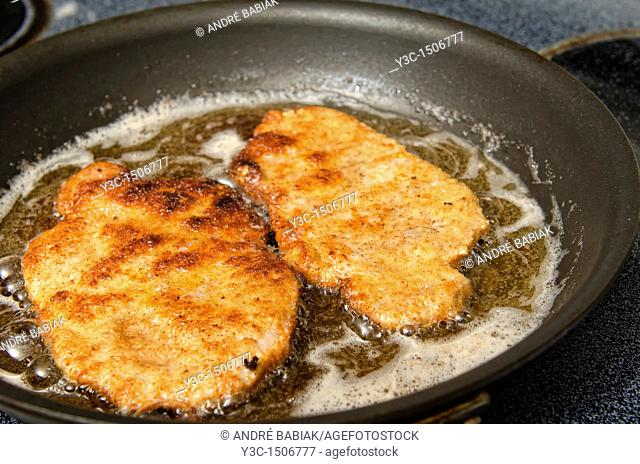 Pan frying Schnitzel - A traditional German dish with breaded meat