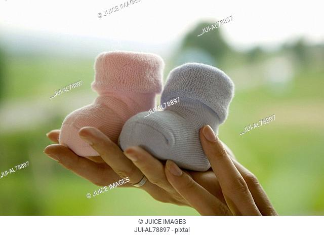 Woman holding up two baby boots