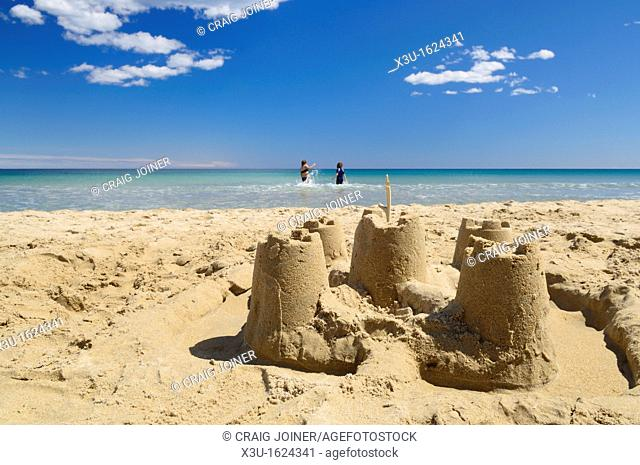 Sandcastles on a sandy beach on a perfect sunny summers day while children play in the sea