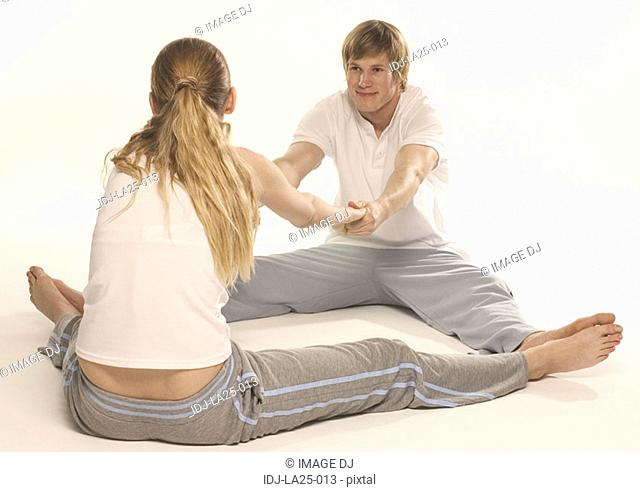 Young woman exercising with a young man on the floor