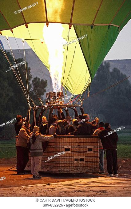 Hot air balloon, jet of flame and passengers prepare to ascend at dawn over the Valley of the Kings and Queens, Al Asasif, Luxor, Egypt, Africa